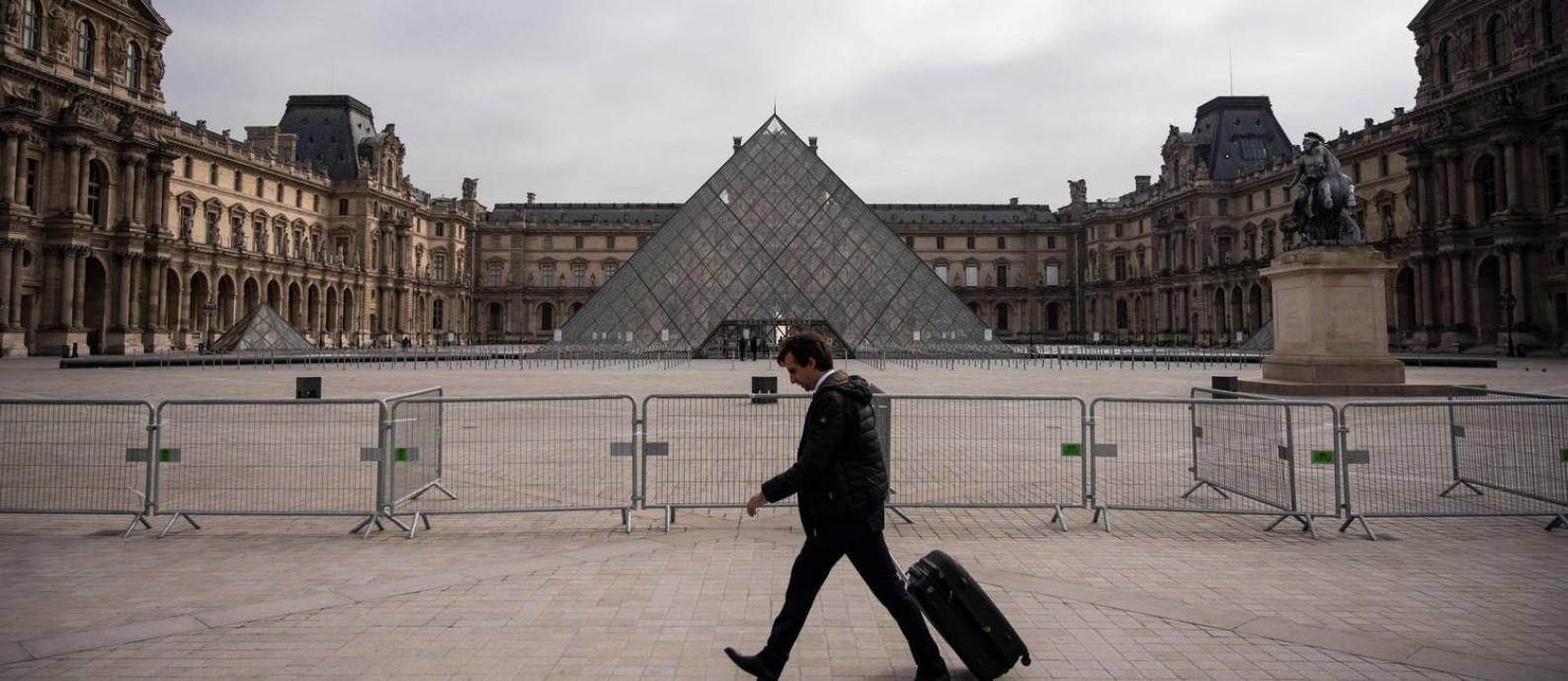 Homem caminha em frente ao Museu do Louvre, em Paris, fechado para visitação pela pandemia de Covid-19 Foto: LIONEL BONAVENTURE / AFP
