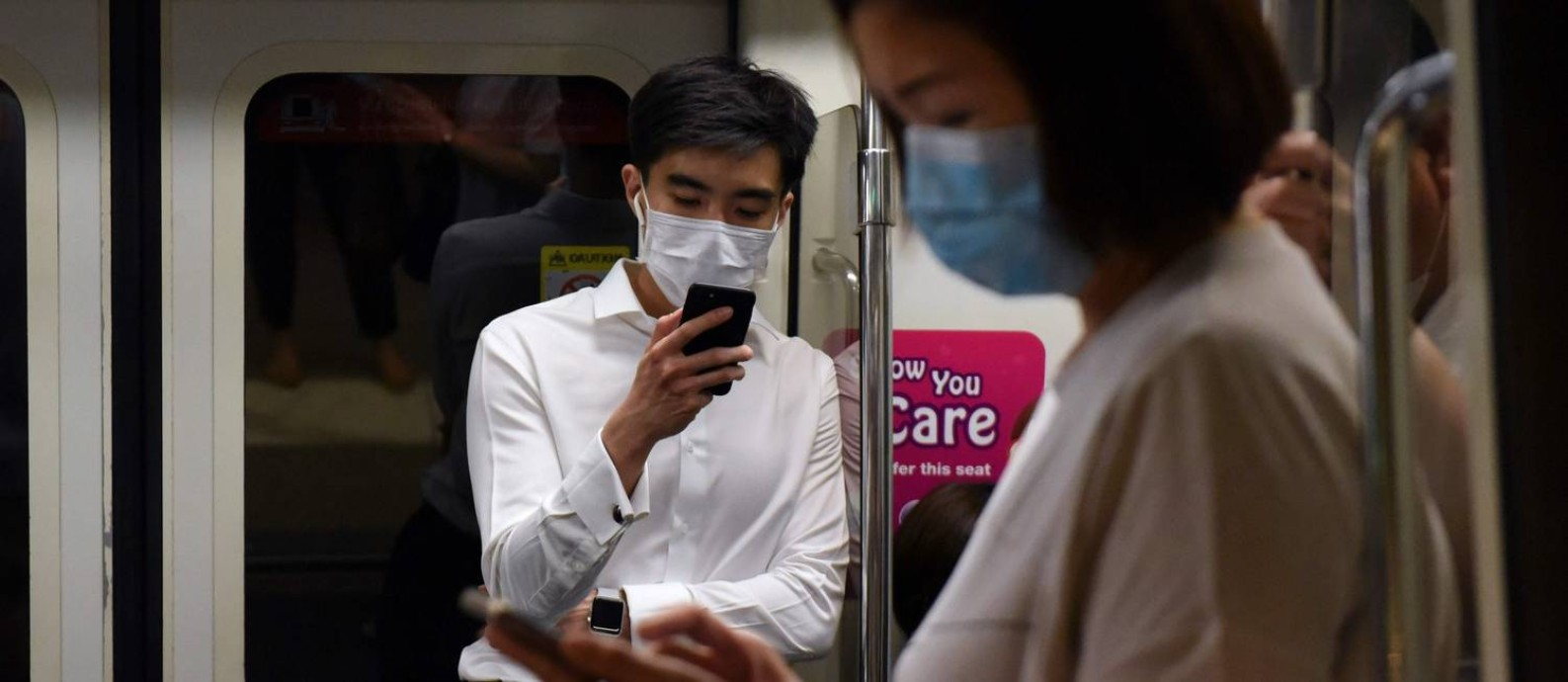 Usuários dos trens rápidos de Cingapura usam máscaras para se proteger da Covid-19 Foto: CATHERINE LAI / AFP