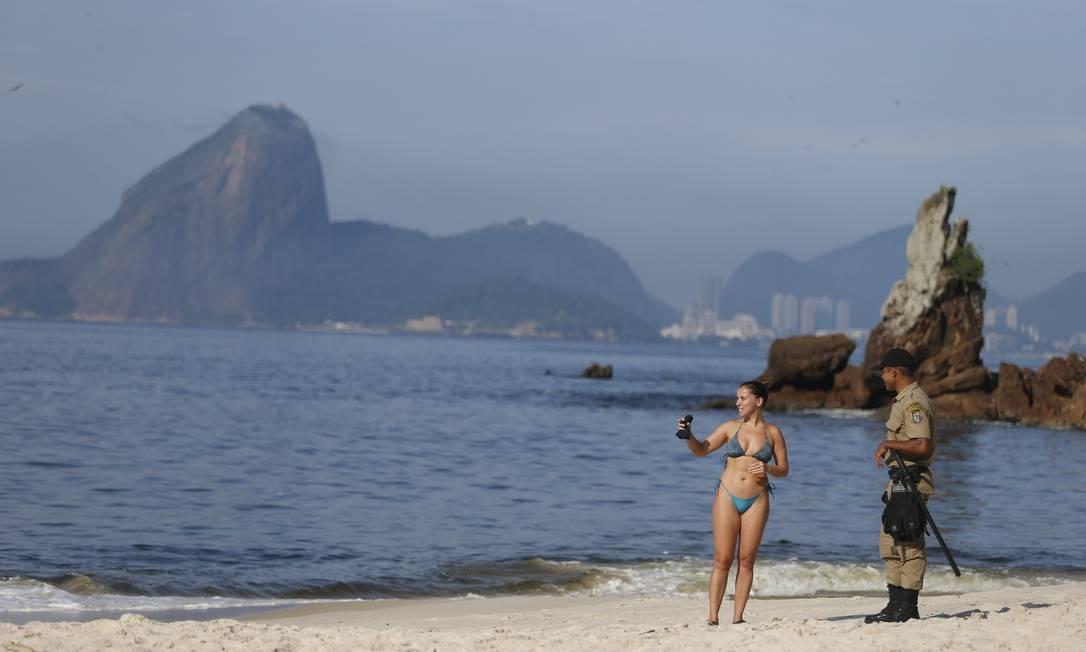 Banhista é orientada a deixar Praia de Icaraí, como medida preventiva à pandemia Foto: Fabiano Rocha / Agência O Globo