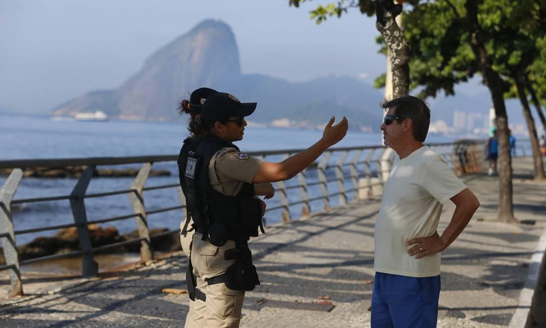 Agente da Guarda Municipal aborda pedestre que estava caminhando no calçadão Foto: Fabiano Rocha / Agência O Globo