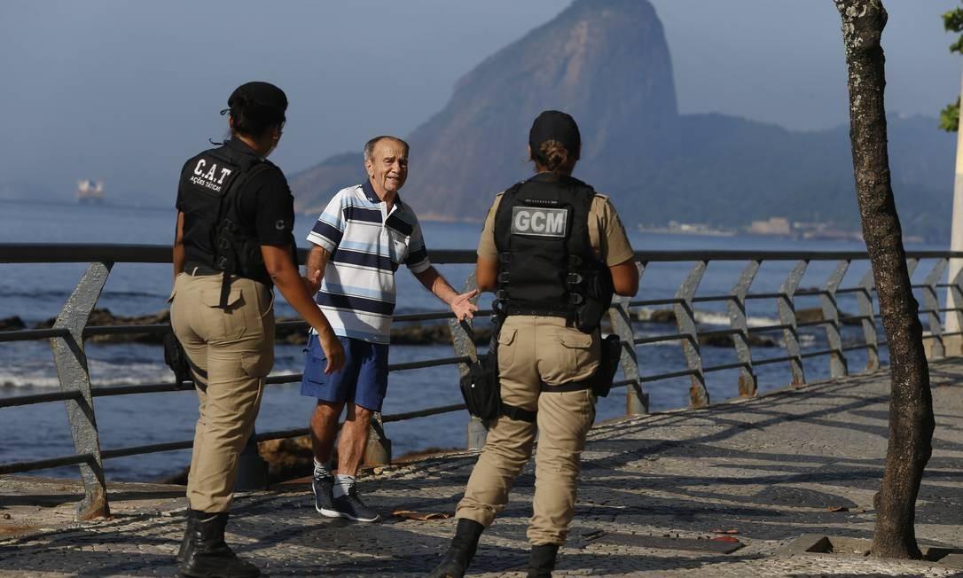 Guardas municipais orientam idoso a sair do calçadão de Icaraí em razão da pandemia de coronavírus Foto: Fabiano Rocha / Agência O Globo