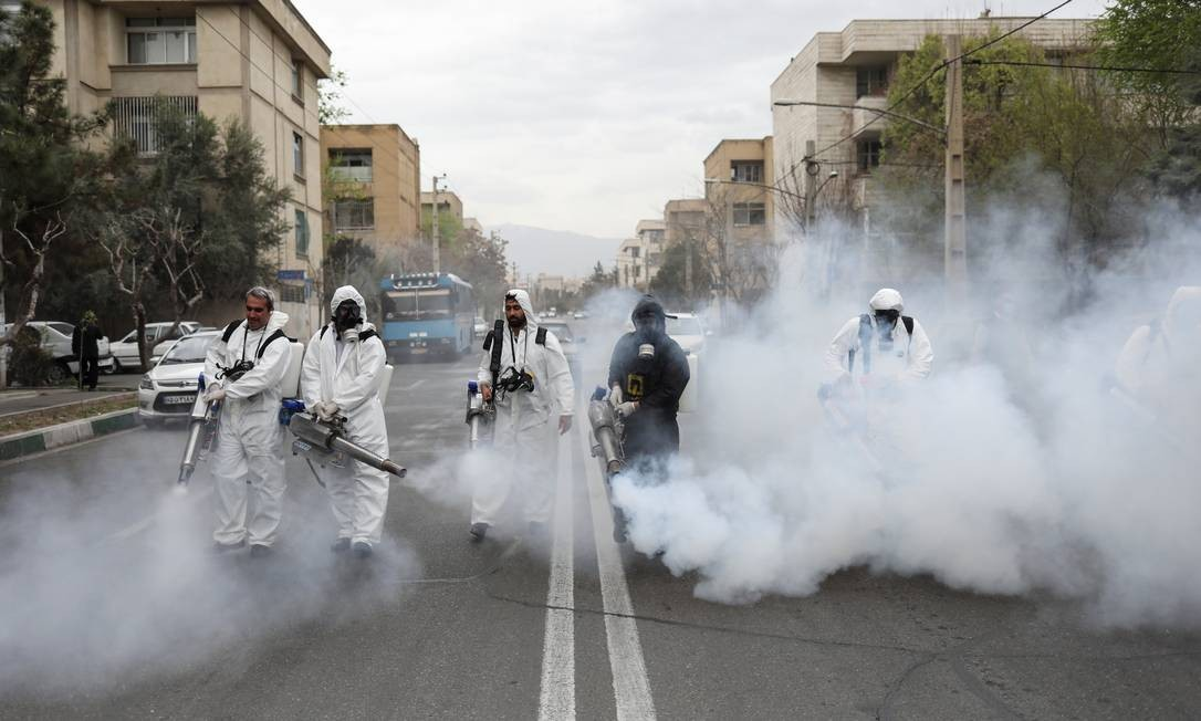 Membros do Corpo de Bombeiros iraniano desinfetam rua da capital Teerã contra o novo coronavírus Foto: WANA NEWS AGENCY / VIA REUTERS