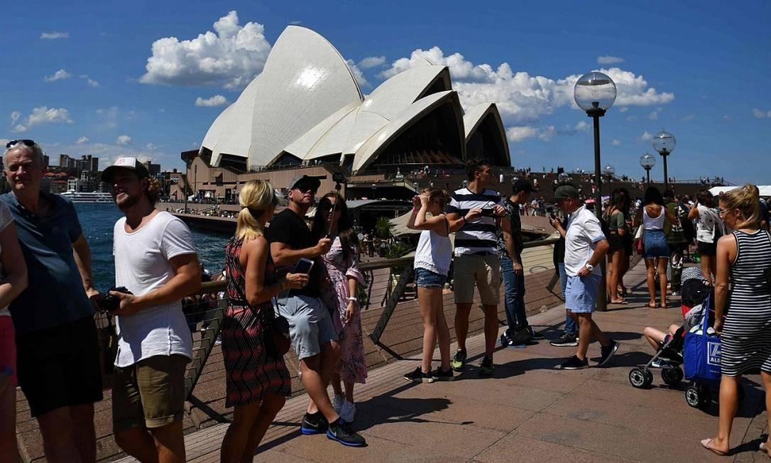 Antes: uma multidão de turistas em frente à Opera House, um dos símbolos de Sydney, na Austrália Foto: Saeed Khab / AFP