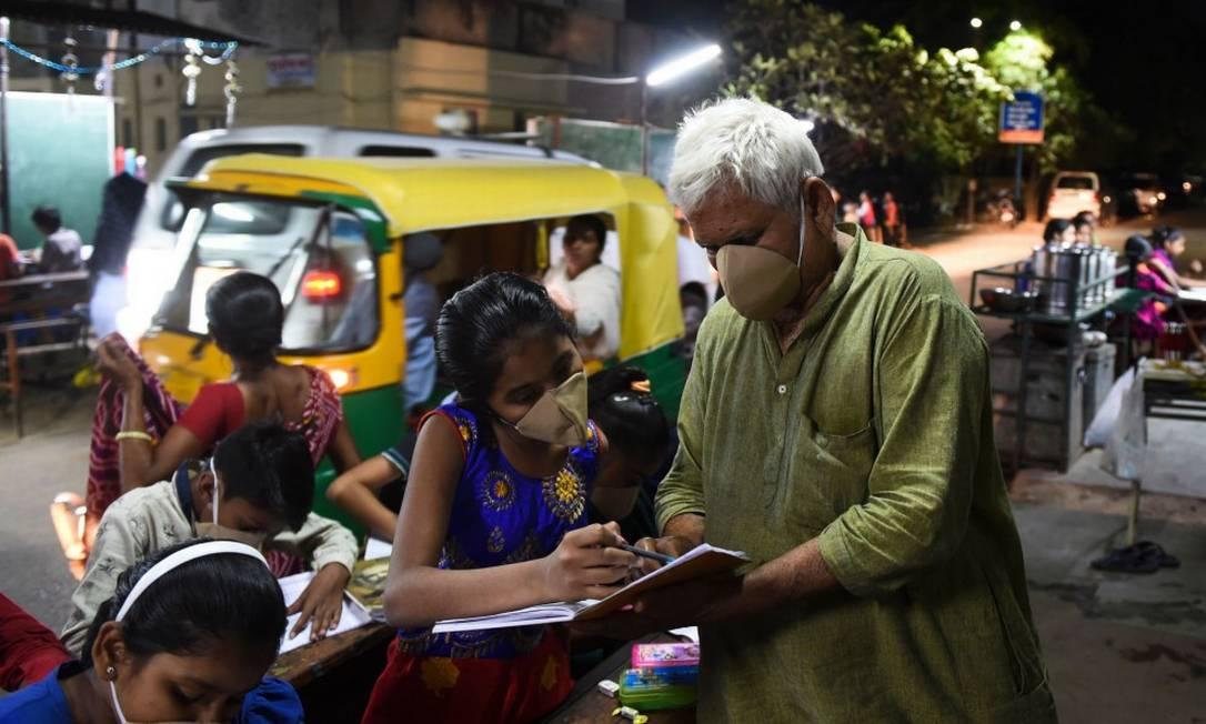 Professor em Ahmedabad, na Índia, usa máscara para ensinar alunos Foto: SAM PANTHAKY / AFP