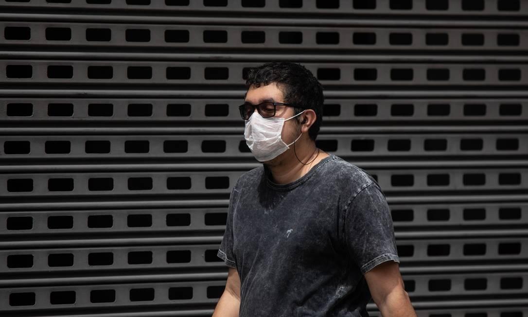 Jovem usa máscara contra corona vírus na Rua de Santanna. Centro do Rio. Foto: BRENNO CARVALHO / Agência O Globo