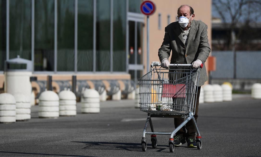 Idoso usando uma máscara protetora empurra seu carrinho quando chega para fazer compras em um supermercado em Codogno, sudeste de Milão, depois que a Itália impôs restrições nacionais aos seus 60 milhões pessoas para controlar a Covid-19. Itália é um país de idosos, o mais antigo da Europa, segundo as estatísticas, e poucos deles moram em casas de repouso, a questão de seu isolamento é aguda Foto: MIGUEL MEDINA / AFP