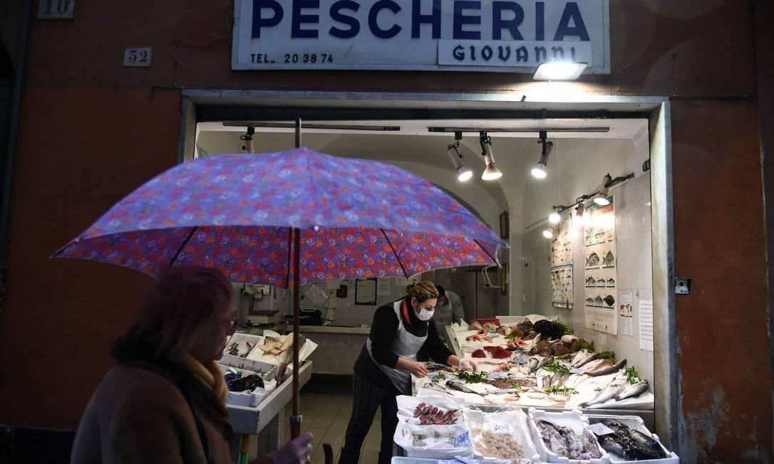 Idosa passa por uma peixaria da histórica Gênova Foto: MARCO BERTORELLO / AFP