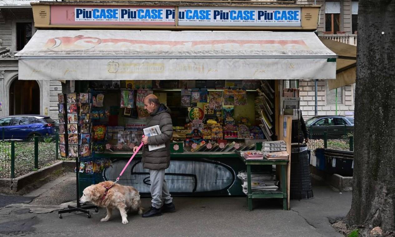 Iidoso passeia com seu cachorro e compra um jornal em uma banca em Milão. Itália determinou fechamento de todas as lojas, exceto farmácias e lanchonetes, numa tentativa desesperada de impedir a propagação do novo coronavírus. País registra cerca de 3 mil mortos pela Covid-19 Foto: MIGUEL MEDINA / AFP