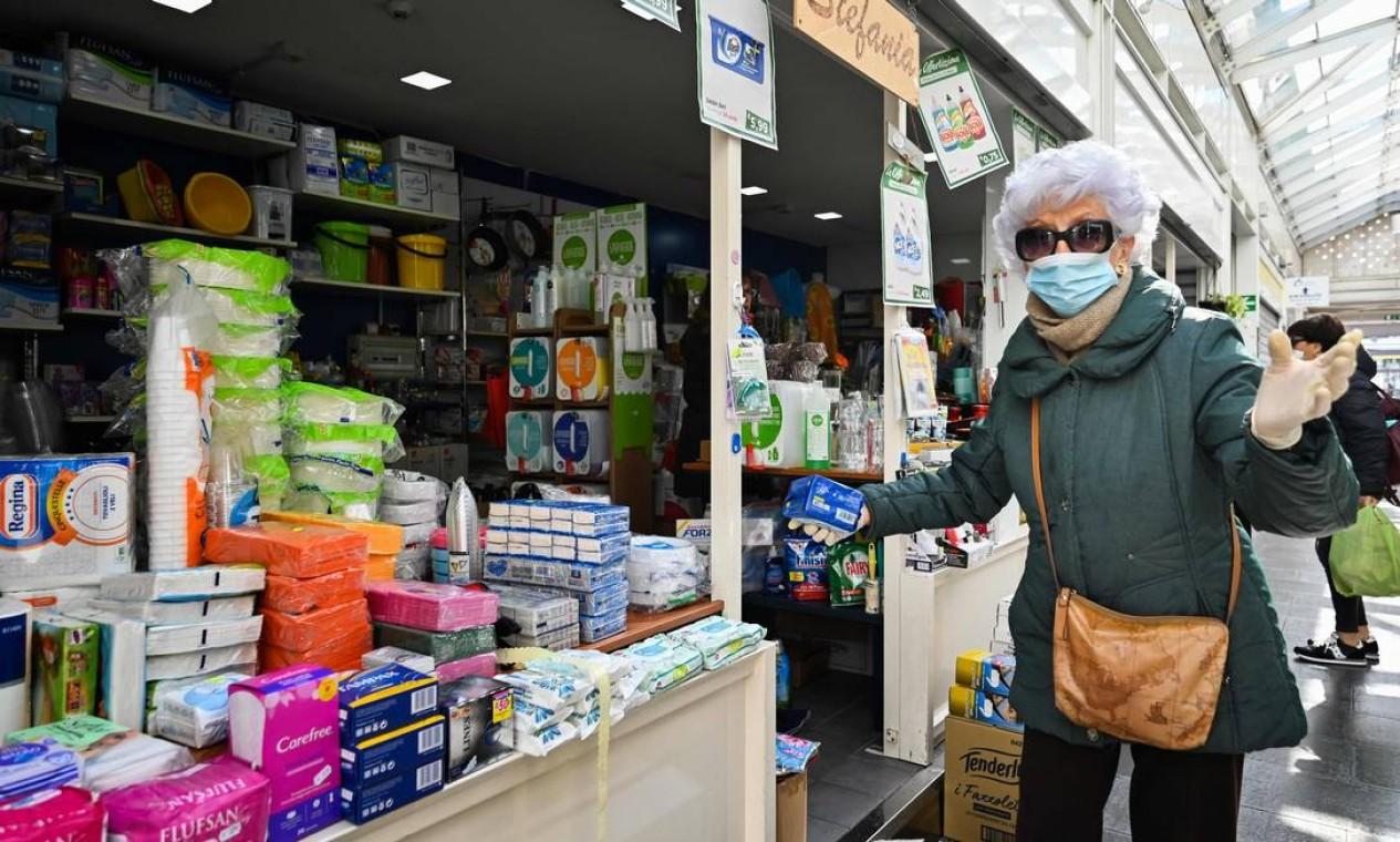Idosa faz compra em uma banca de utensílios domésticos de um mercado em Roma durante confinamento Foto: ALBERTO PIZZOLI / AFP