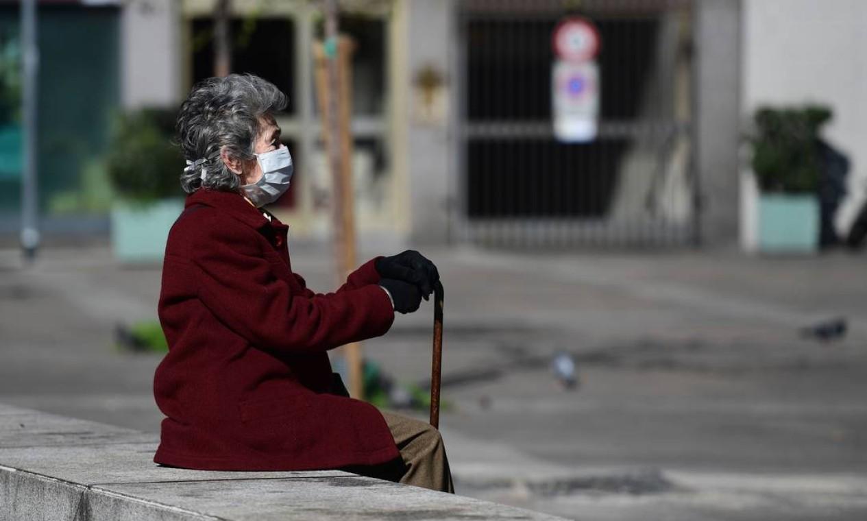 Iidosa com máscara protetora senta-se em um banco no centro de Milão. Isolamento dos idosos está na ordem do dia, pois a Itália tem a população mais envelhecida da Europa Foto: MIGUEL MEDINA / AFP