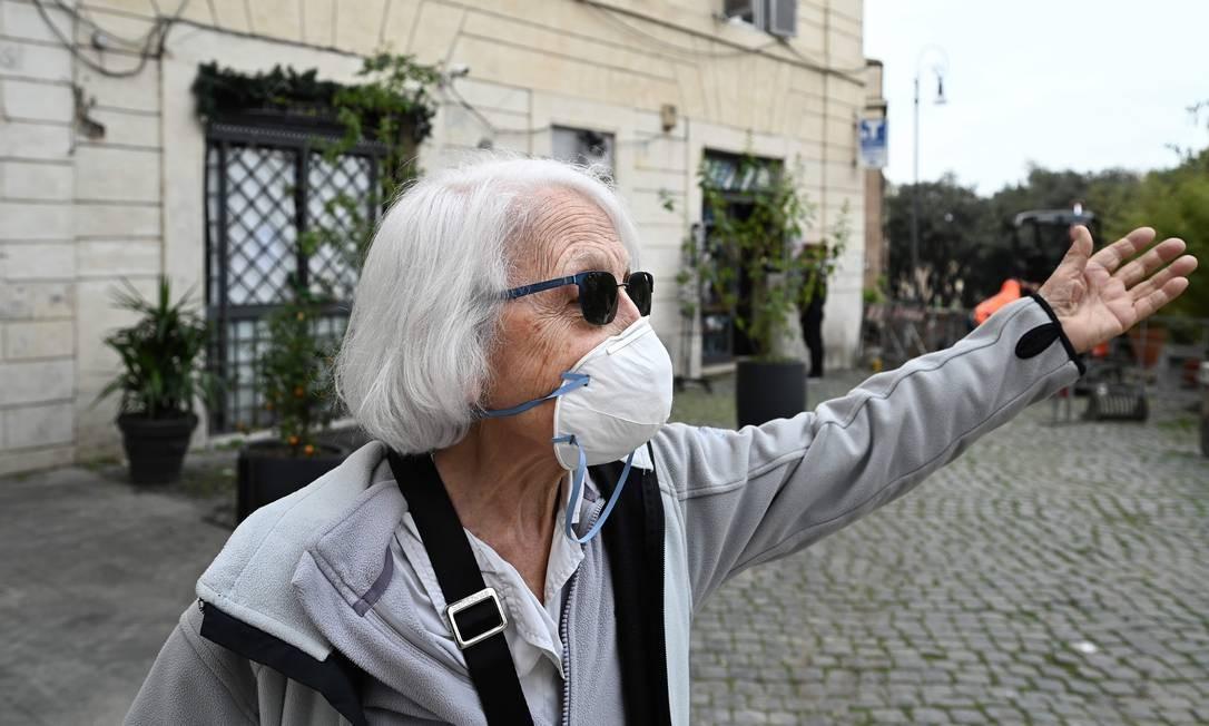 Idosa de 83 anos usa máscara facial quando sai para fazer compras no centro de Roma. Mais vulneráveis, idosos são o alvo favorito do coronavírus: falecidos na Itália têm idade média de 80 anos Foto: VINCENZO PINTO / AFP