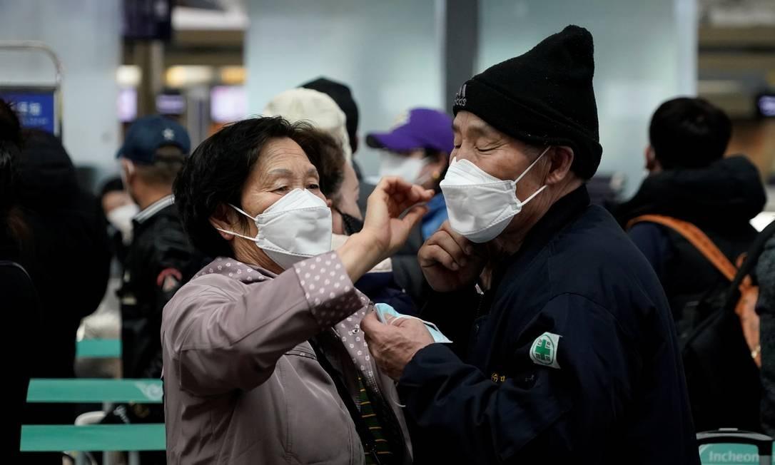 Mulher ajusta máscara do marido no Aeroporto Internacional de Incheon, na Coreia do Sul: país conseguiu dobrar curva de crescimento de casos de coronavírus Foto: KIM HONG-JI/REUTERS