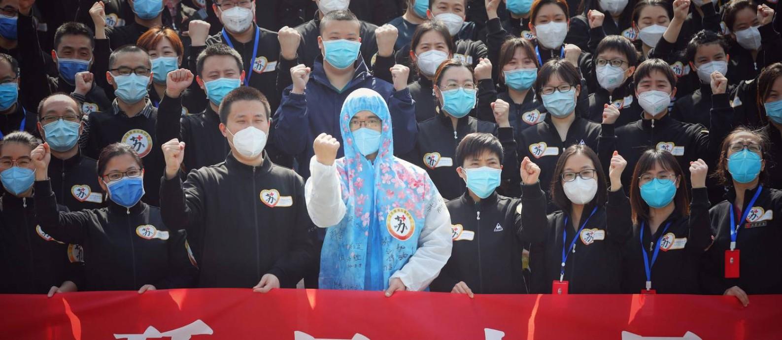 Profissionais da saúde chineses participam de cerimônia Foto: STR / AFP