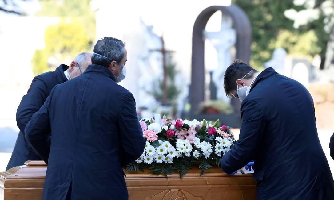 Homens com máscaras de proteção carregam caixão de vítima do novo coronavírus em cemitério de Bergamo, na Itália Foto: Flavio Lo Scalzo / REUTERS
