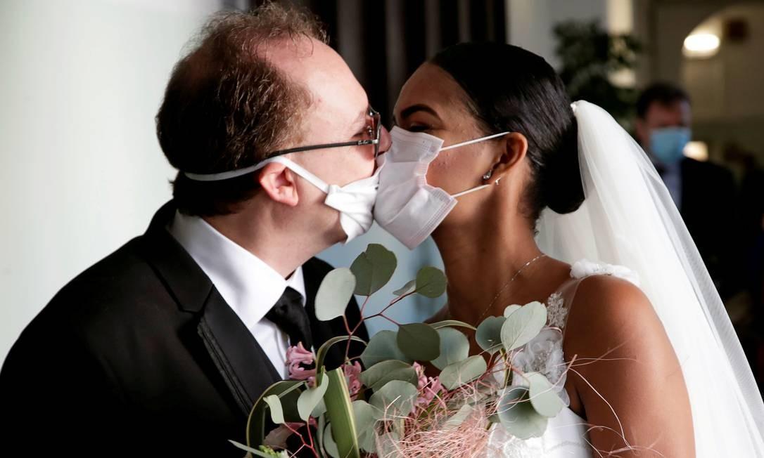 Os recém-casados Diego Fernandes, 46 anos, e Deni Salgado, 30 anos, se beijam com máscaras protetoras em uma cerimônia de casamento com apenas testemunhas legais, sem convidados, em Nápoles, Itália Foto: Ciro de Luca / Reuters