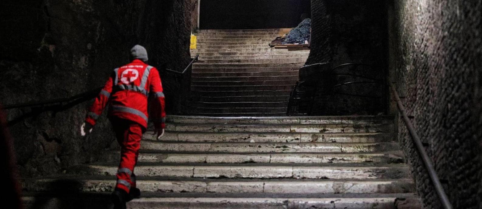 Voluntário da Cruz Vermelha checa condição de moradores de rua em área próxima ao Coliseu, em Roma, na Itália Foto: GUGLIELMO MANGIAPANE / REUTERS