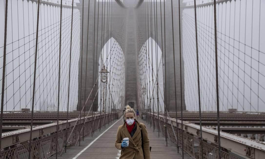 Jovem vestindo máscara atravessa a Ponte do Brooklyn, em Nova York Foto: Victor J. Blue / AFP