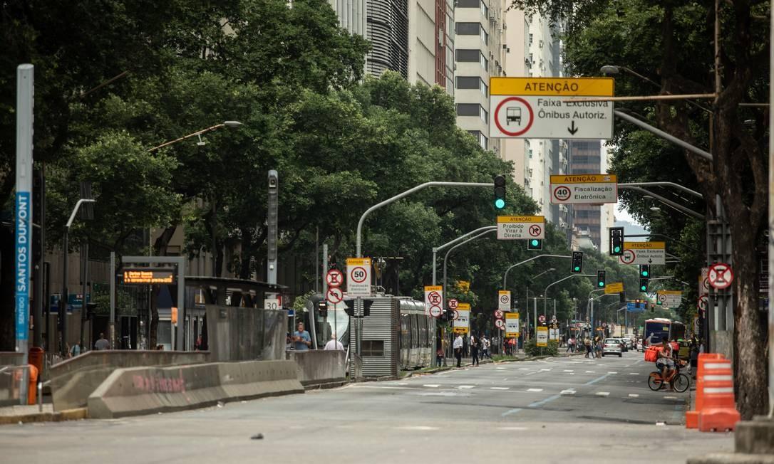 Cena incomum até mesmo em feriados: Avenida Rio Branco com movimento bem pequeno de carros e pessoas circulando pelo Centro Foto: Brenno Carvalho / Agência O Globo