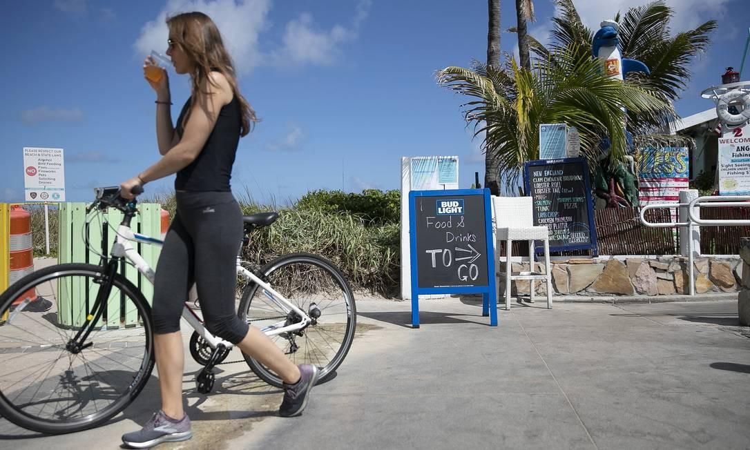 Ciclista passeia por pier na Flórida: um terço dos infectados nos EUA são jovens Foto: JOE RAEDLE / AFP
