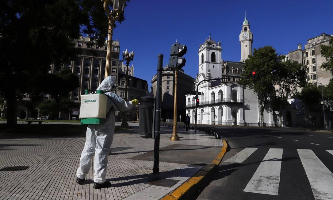 Homem desinfeta a Praça de Maio: argentinos estão em casa Foto: MATIAS BAGLIETTO / REUTERS