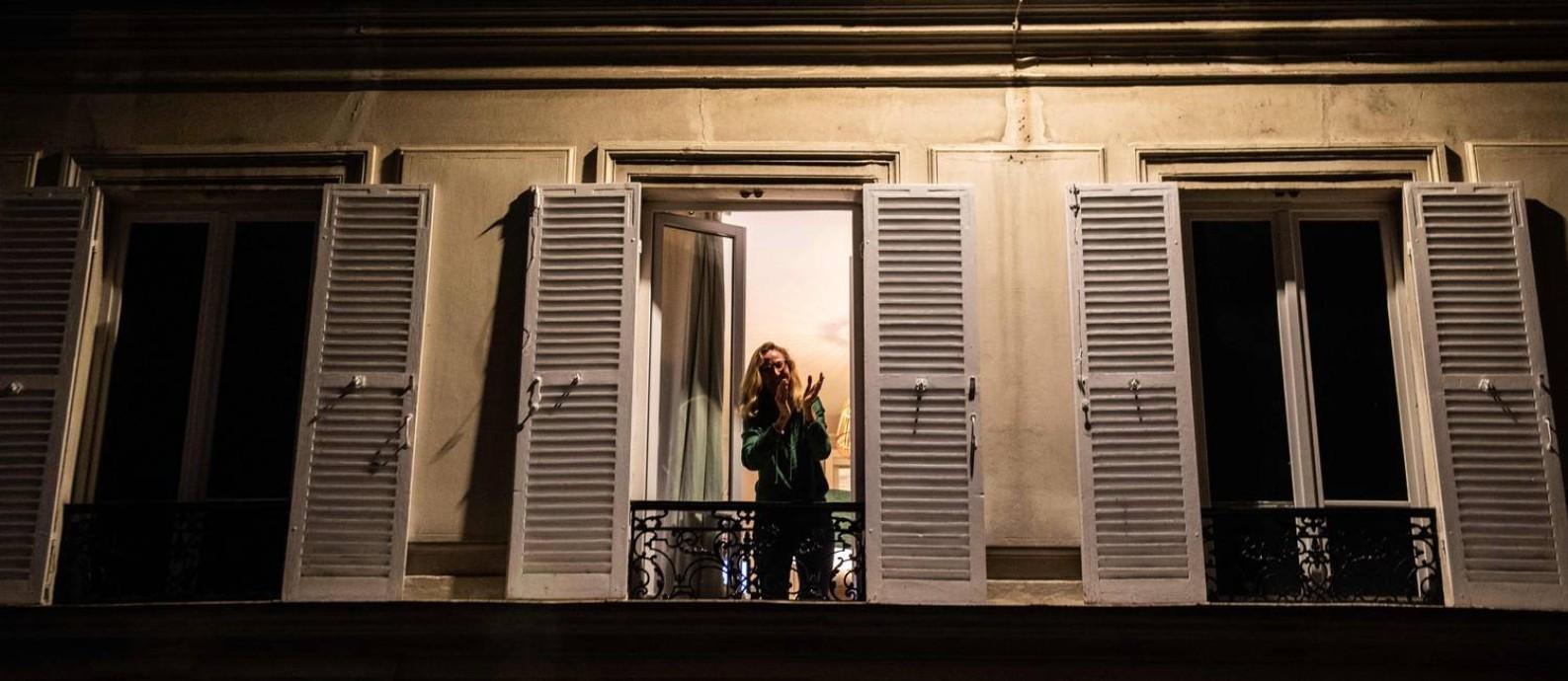 Recolhidos em casa, parisienses aplaudem os profissionais de saúde que trabalham para conter a Covid-19 Foto: MARTIN BUREAU / AFP