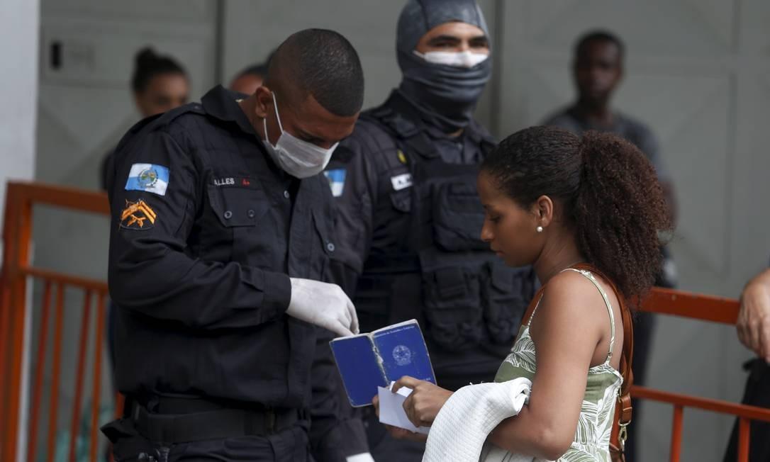 Policial verifica carteira de trabalho de passageira em Niterói neste sábado (21) Foto: Fabiano Rocha / O Globo