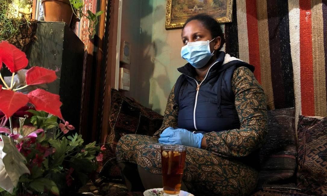 Mulher usa máscara e luva em restaurante da Cidade do Cabo Foto: Sumaya Hisham / REUTERS