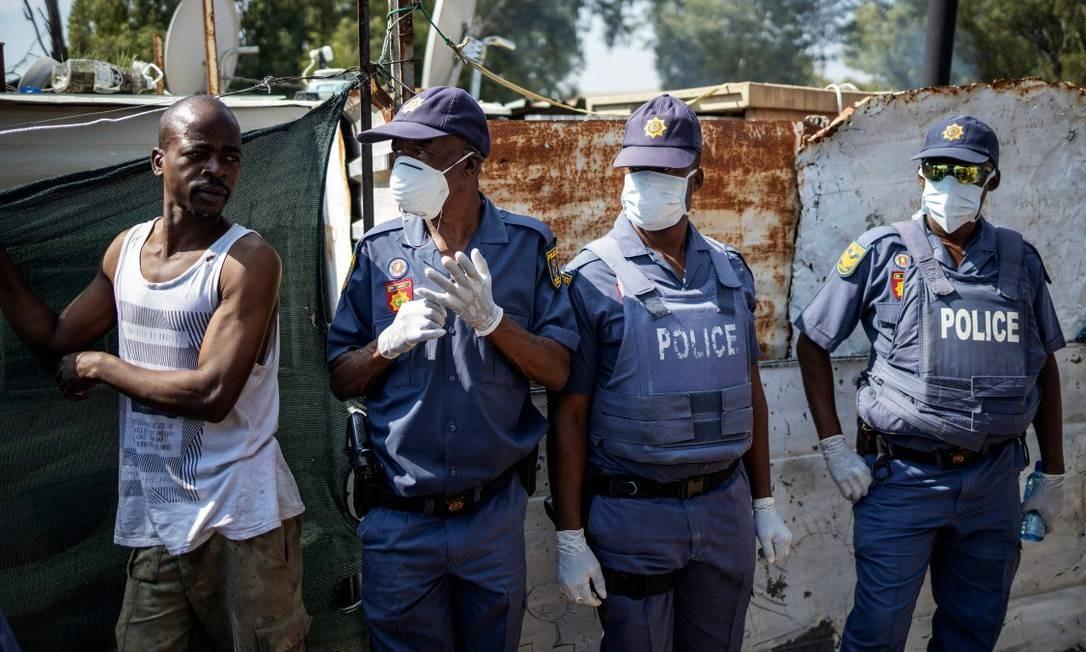 Policiais na África do Sul usam máscaras e luvas Foto: MICHELE SPATARI / AFP