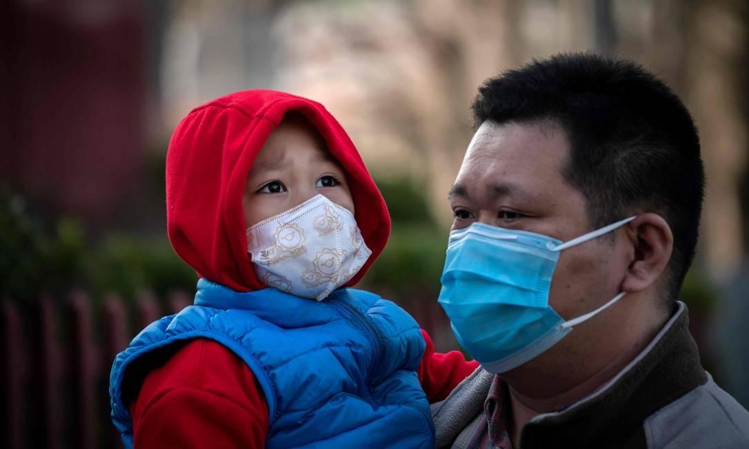 Adultos e crianças usam máscara em Pequim Foto: NICOLAS ASFOURI / AFP