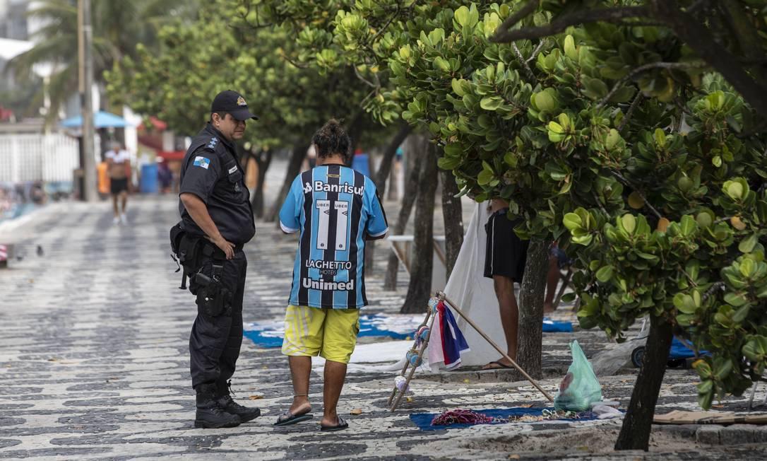 Policial orienta ambulante no calçadão do Posto 8, em Ipanema, a retirar mercadoria Foto: Ana Branco / Agência O Globo
