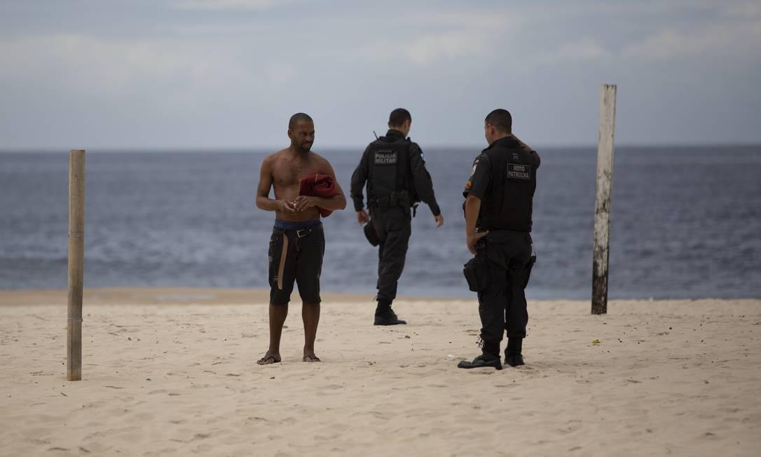 Policiais retiram banhistas de Copacabana, após decreto estadual entrar em vigor proibindo o acesso às praias do Rio Foto: Gabriel Monteiro / Agência O Globo