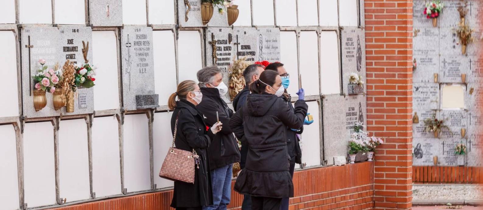 Pessoas participam de enterro de vítima do novo coronavírus portando máscaras em cemitério de Madri, na Espanha; cidade concentra 58% das vítimas fatais no país Foto: BALDESCA SAMPER / AFP