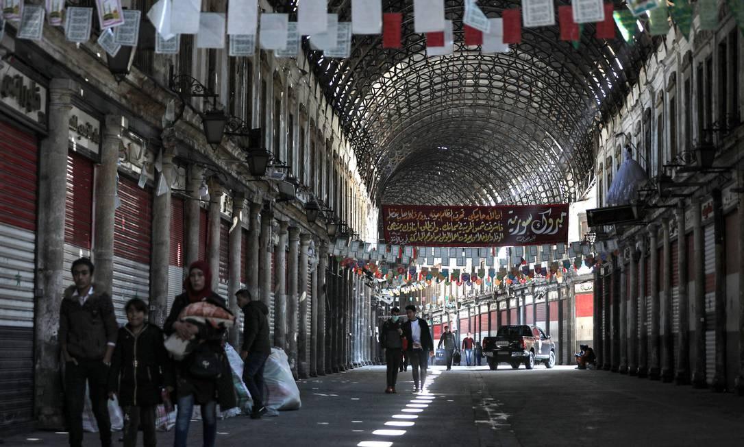 Pessoas caminham no mercado de Hamidiyah, na cidade velha de Damasco. Governo ordenou o fechamento do comércio depois da confirmação do primeiro caso de Covid-19 no país Foto: LOUAI BESHARA / AFP