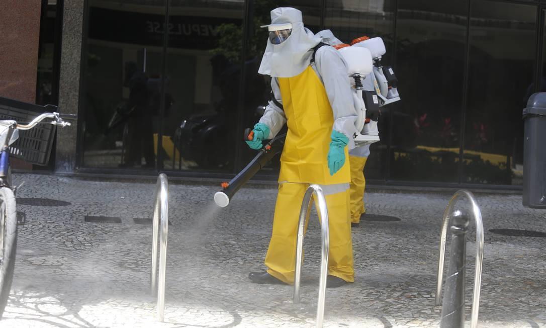 Funcionários da prefeitura de Niterói utilizam o quaternário de amônia para sanitizar a cidade Foto: Fabiano Rocha / O Globo