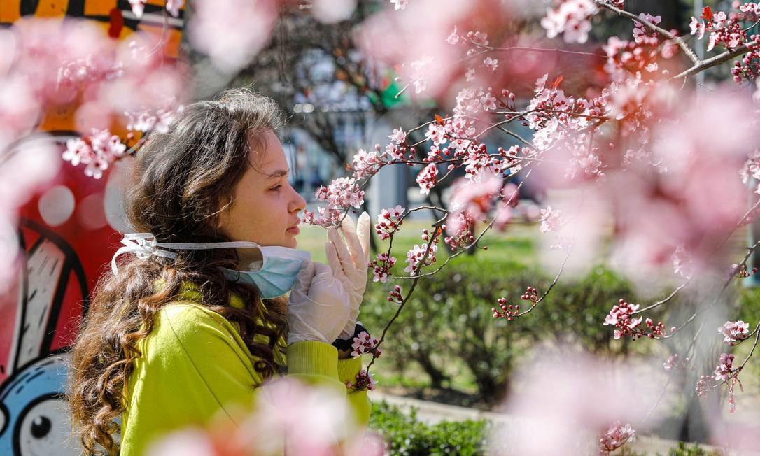 Jovem tira a máscara de proteção contra o novo coronavírus para sentir o cheiro de rosas em árvore de Skopje, capital da Macedônia do Norte Foto: OGNEN TEOFILOVSKI / REUTERS