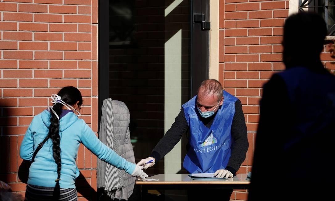 Uma mulher e um voluntário usando máscaras e luvas protetoras aguardam a distribuição de alimentos na paróquia de San Gaudenzio, em Roma, durante isolamento para impedir a propagação da doença Foto: YARA NARDI / REUTERS