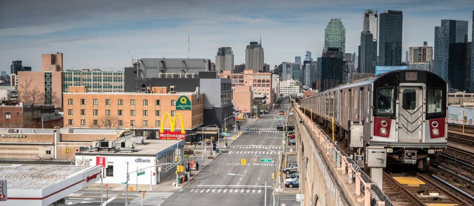 Ruas desertas no distrito de Queens, na cidade de Nova York, contrastam com operação do metrô: governador Andrew Cuomo e prefeito Bill de Blasio são pressionados a adotar medidas ainda mais drásticas Foto: JUAN ARREDONDO / NYT