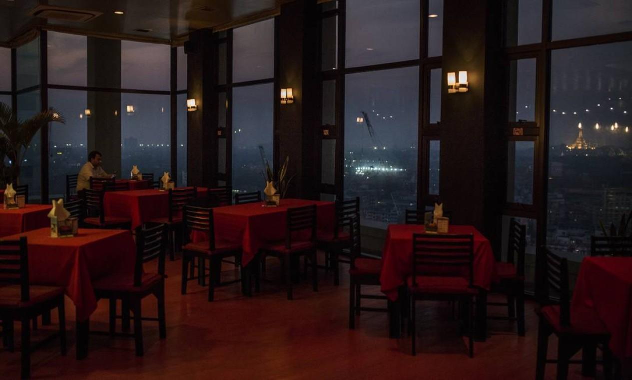 Um restaurante quase vazio que antes era popular entre os turistas pela vista panorâmica do centro de Yangon, Mianmar Foto: Minzayar Oo / NYT