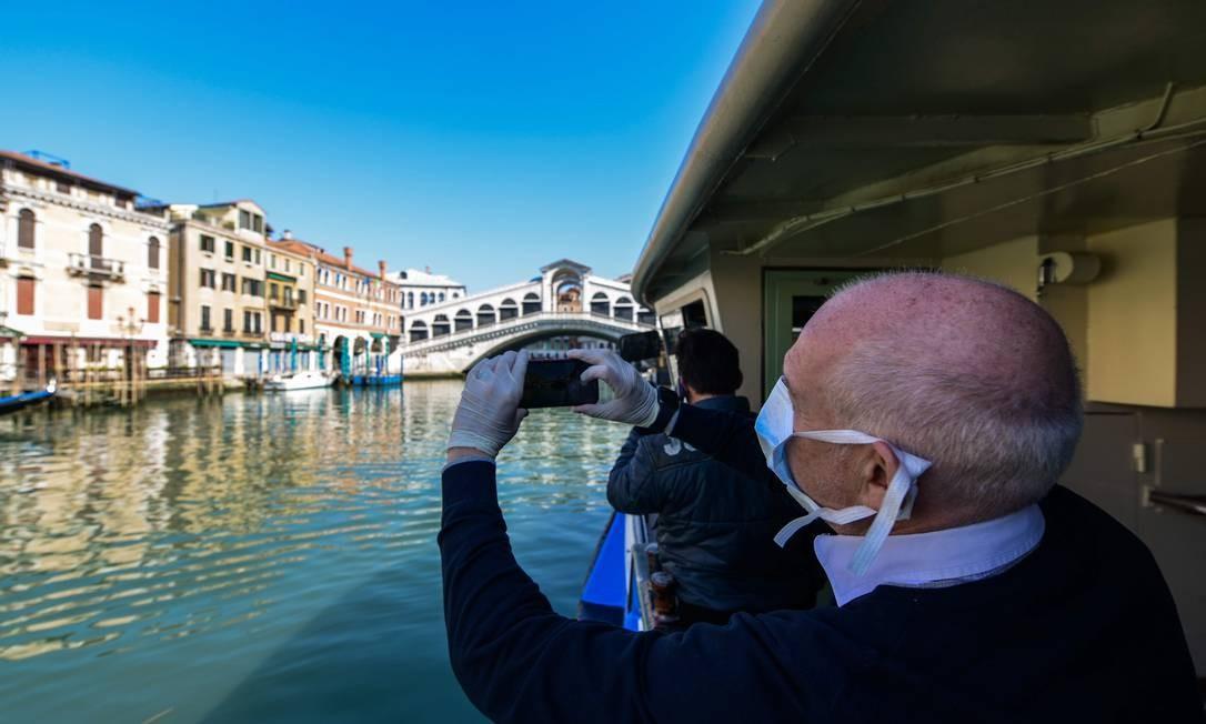 Homem usando máscara fotografa passageiros de uma balsa em Veneza: águas mais limpas após restrições a circulação de pessoas Foto: ANDREA PATTARO/AFP/18-3-2020