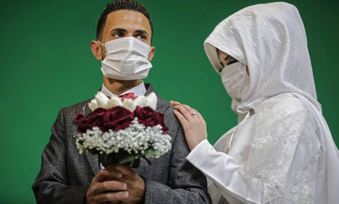 Casal palestino Mohamed Abu Daga e Israa usam máscaras protetoras em um estúdio de fotografia, antes da cerimônia de casamento, em Khan Yunis, no sul da Faixa de Gaza, depois que autoridades confirmaram os dois primeiros casos da Covid-19 – pessoas que viajaram para o Paquistão e estavam em quarentena desde seu retorno Foto: Said Khatib / AFP