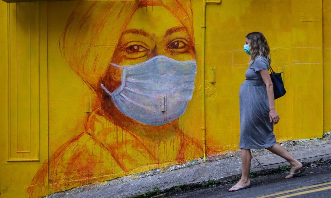 Mulher grávida usando uma máscara facial como medida de precaução passa por um mura de arte urbana,l em rua de Hong Kong. A partir desta terça-feira não residentes estão proibidos de entrar no território semiautônomo da China Foto: Anthony Wallace / AFP