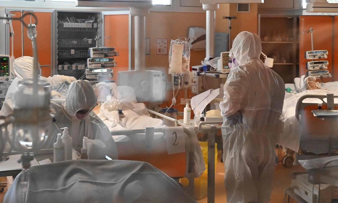 Médicos e enfermeiros vestem roupas de proteção em unidade de terapia intensiva de nível 3 voltada para pacientes de Covid-19 em hospital nos arredores de Roma, capital da Itália Foto: ALBERTO PIZZOLI / AFP