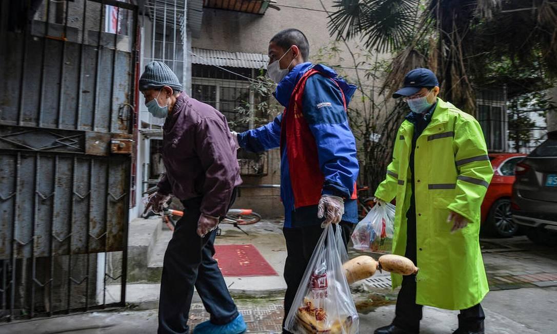 Dois voluntários acompanham um idoso em Wuhan, na China Foto: AFP