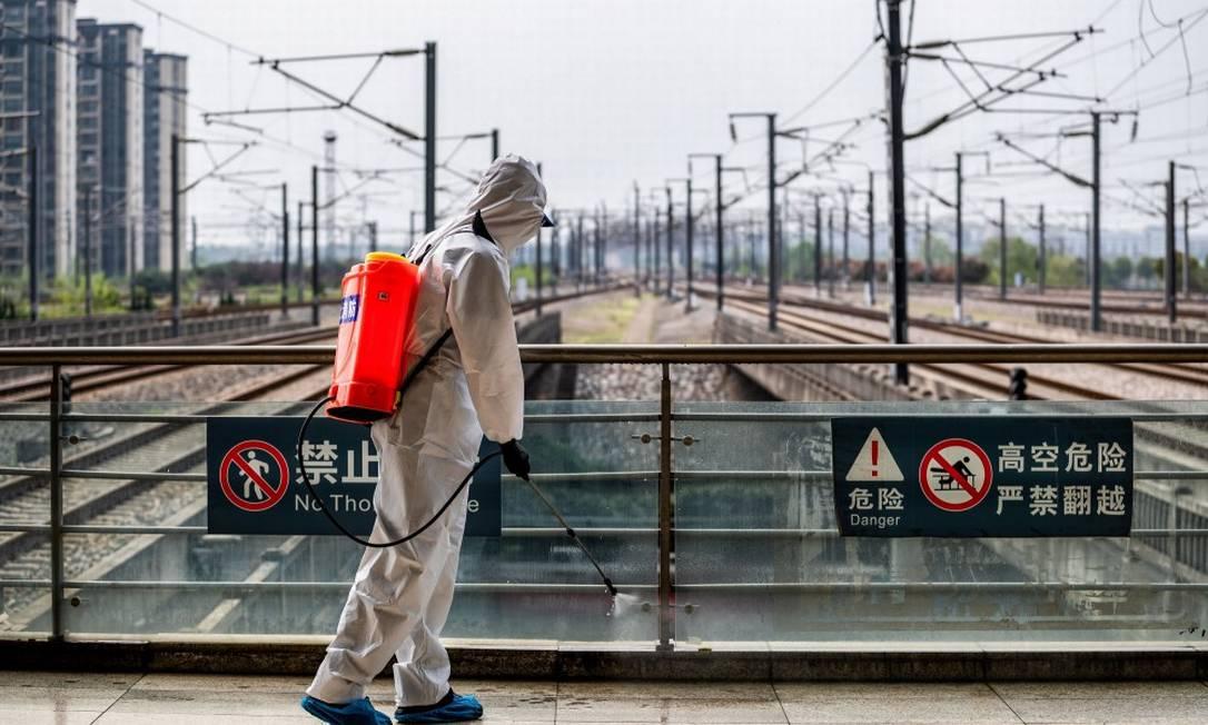 Homem desinfecta ferrovia na cidade de Wuhan, em Hubei Foto: STR / AFP / 24-03-2020