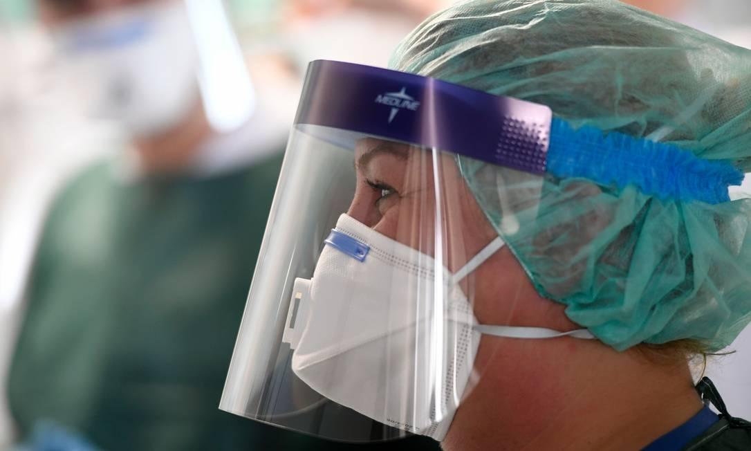 Enfermeira usa máscara e equipamento de proteção em hospital em Essen, na Alemanha Foto: INA FASSBENDER / AFP