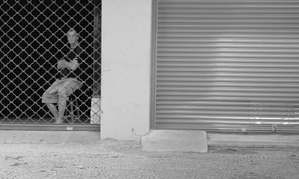 De dentro de uma loja com portas fechadas, um homem observa a Siqueira Campos, em Copacabana, vazia Foto: Márcia Foletto / Agência O Globo