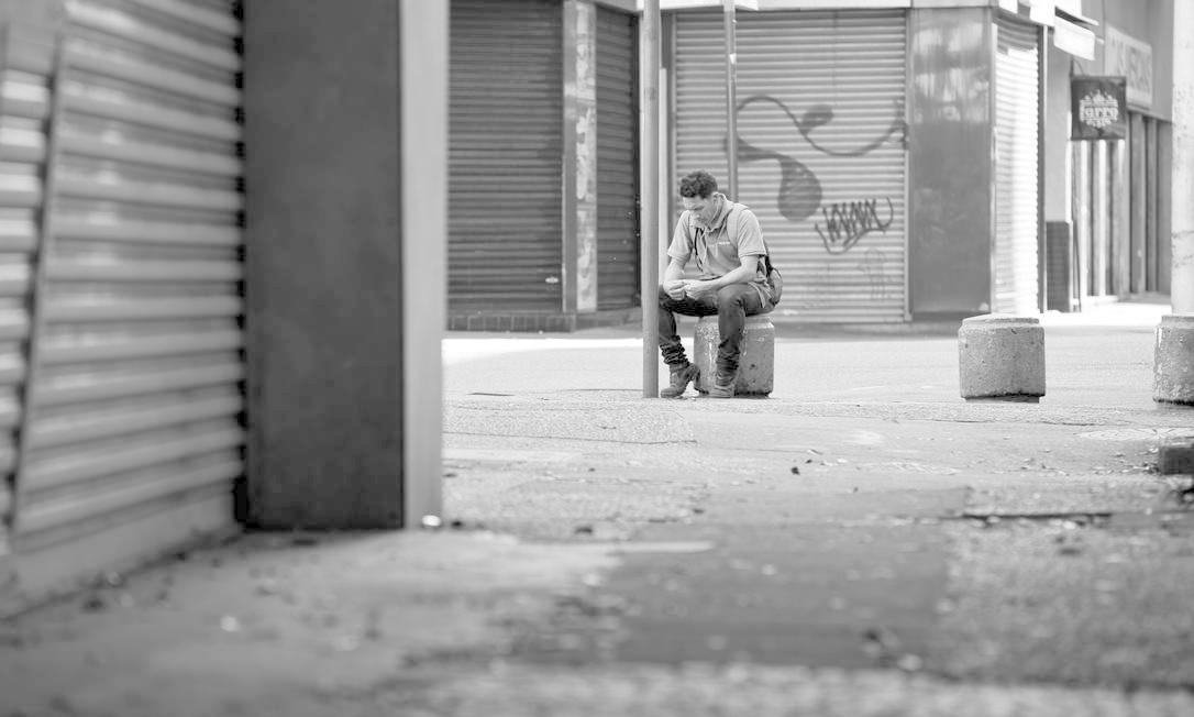 Um homem senta-se em meio a ruas vazias e lojas fechadas na Avenida Nossa Senhora de Copacabana. Decreto municipal que determina o fechamento dos estabelecimentos comerciais na cidade do Rio passa a valer a partir desta terça-feira (24) Foto: Márcia Foletto / Agência O Globo