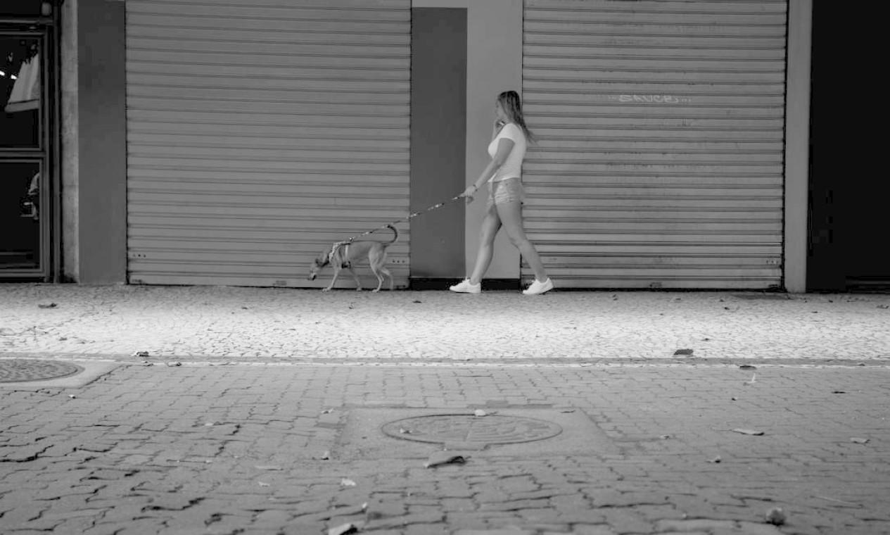 Mulher passeia com seu cão na Visconde de Pirajá, em Ipanema, onde portões das lojas se encontram fechados Foto: Márcia Foletto / Agência O Globo