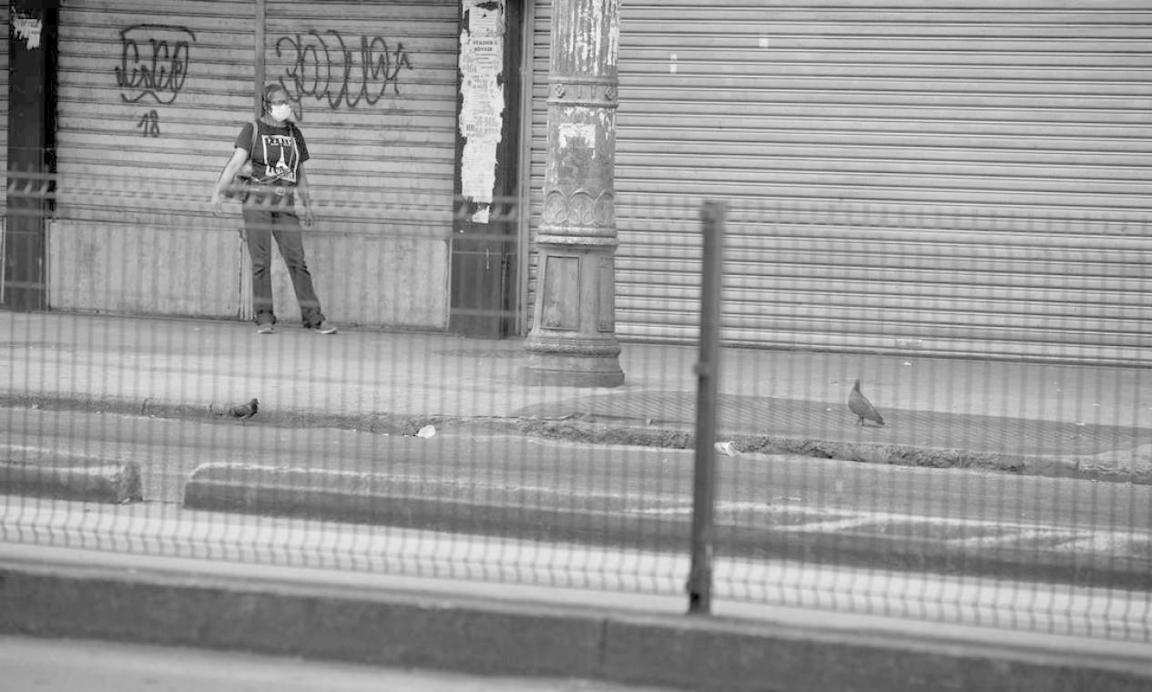 Na Avenida Edgar Romero, em Madureira, mulher espera por ônibus na via deserta Foto: Márcia Foletto / Agência O Globo