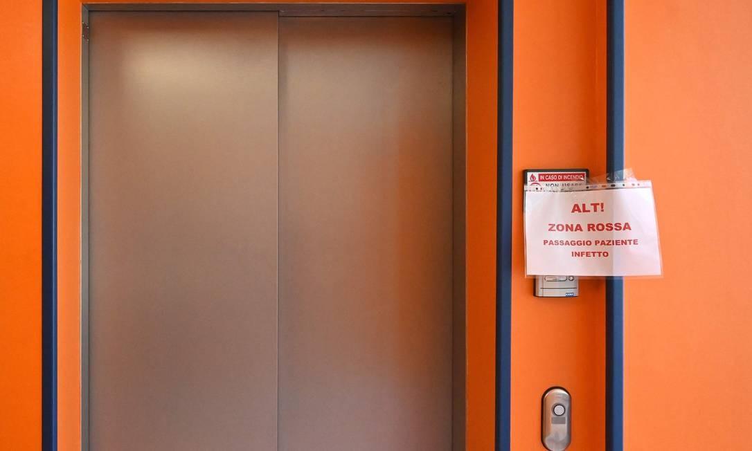 """Um cartaz colado no elevador sinaliza: """"Pare! Zona vermelha, passagem de pacientes infectados"""", dentro da nova unidade de terapia intensiva Covid 3, no hospital Casal Palocco, perto de Roma Foto: ALBERTO PIZZOLI / AFP"""